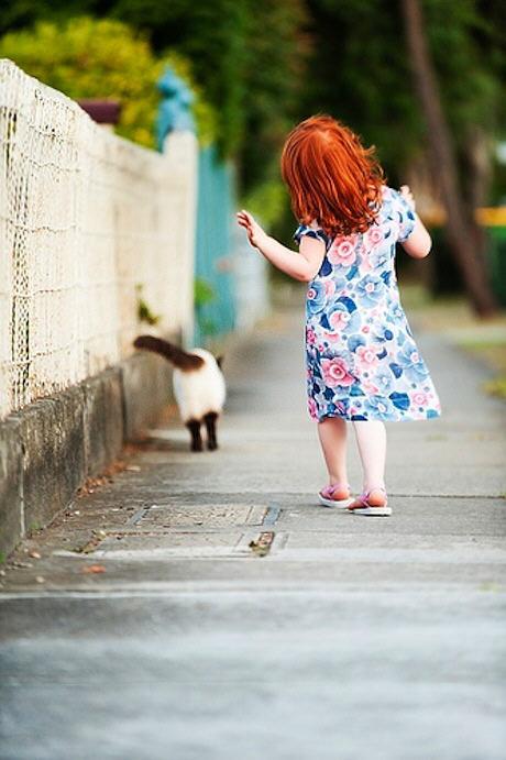 Foto de una niña y su gato caminando muy tranquilos