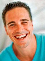 Um homem jovem, sorrindo.
