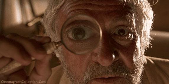Um homem velho, olhando através de uma lupa.