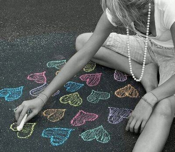 Uma menina desenhando com giz corações no chão.