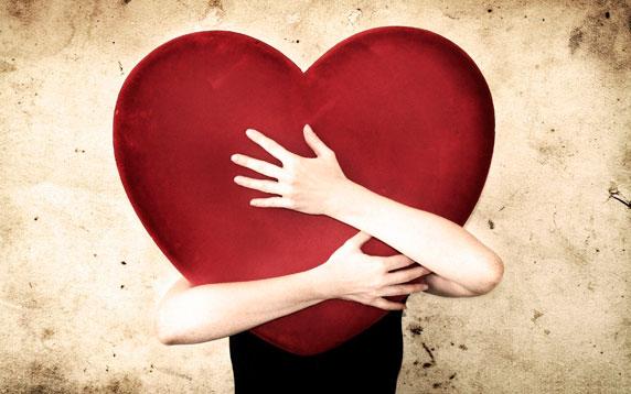 Una mujer que abraza un gran corazón