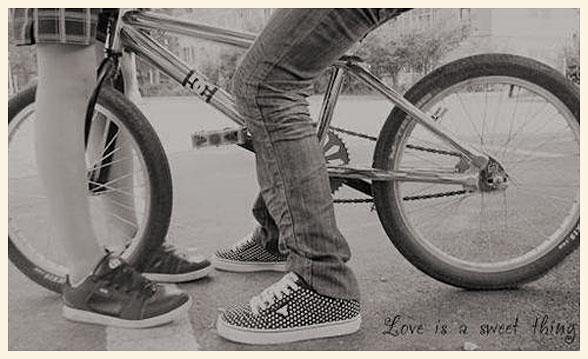 Una pareja muy joven, junto a una bicicleta.
