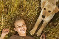 Foto de uma menina feliz acordando junto ao seu cachorro