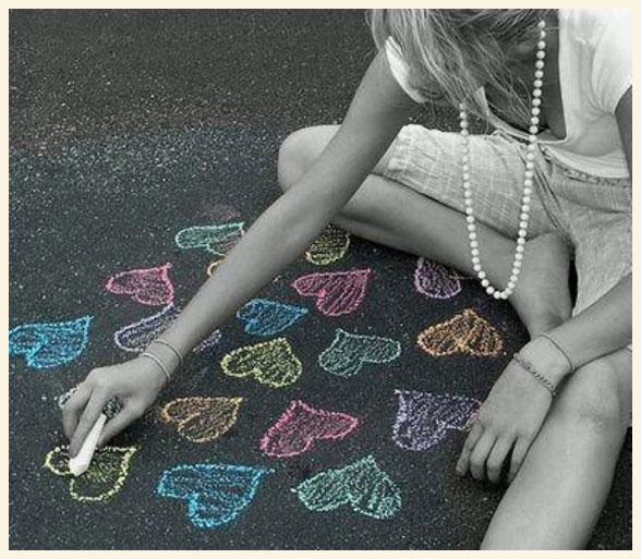 Una chica dibujando corazones con tiza en el suelo.