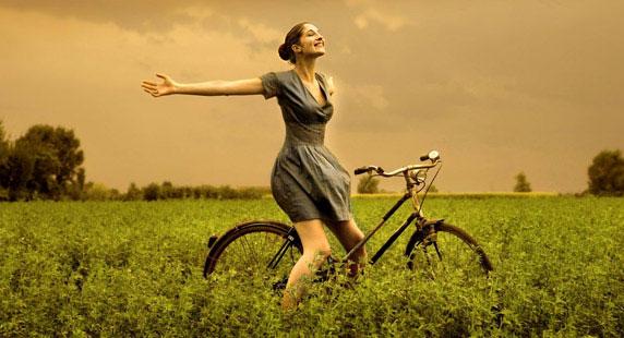 Imagen de una mujer feliz, en el campo, con su bicicleta